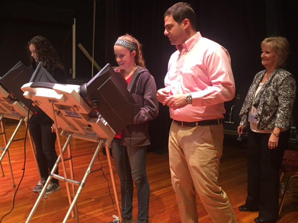Director of elections Cindy Callahan and Daniel Chalupsky, of ElectionIQ, LLC, instruct students on the voting machines.