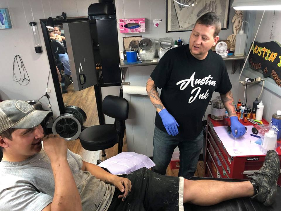 Logan Means, of Knox, (participant in event) getting talking with Ric Austin while getting tattooed.