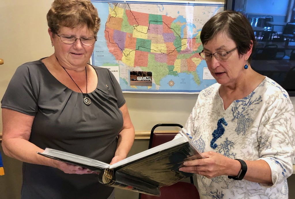 Rotarian Cathy Glosser (left) examines one of many photo albums presented at Monday's meeting of the Clarion Rotary Club.