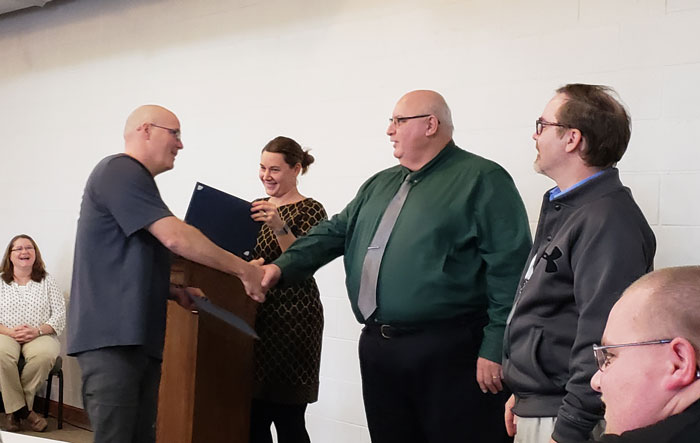 Clarion County Commissioners Ed Heasley and Wayne Brosius congratulate Officer Shawn Zerfoss of the Clarion Borough Police on completion of the CIT program.