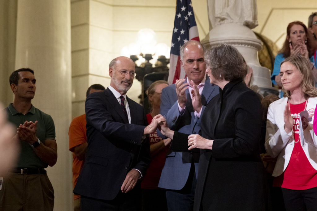 Governor Tom Wolf holds hands with First Lady Frances Wolf after discussing his plan to reduce gun violence at the Harrisburg Capitol on August 7, 2019.