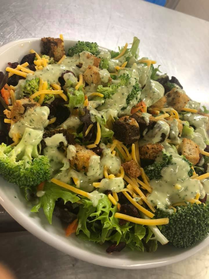 Broccoli and cranberry salad with bacon garlic rye croutons, topped with an homemade cilantro lime yogurt dressing .