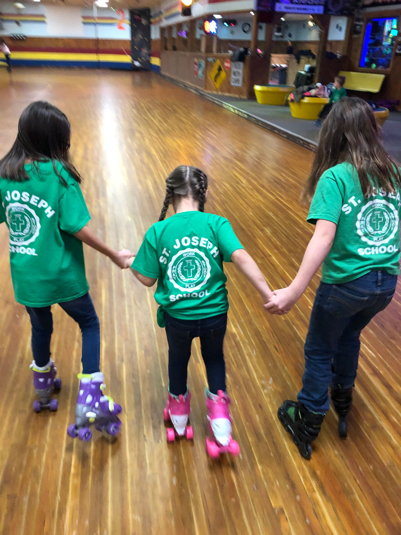 St. Joseph's Elementary students Ellie Williams and Elin Siegel helping Addie Williams around the rink during an event for Catholic Schools Week this week. Submitted by Jennifer Williams.