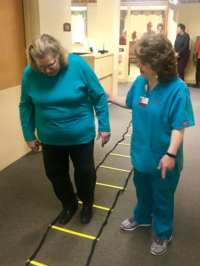Pictured are community member Sherry Neely and Guardian Rehab's Tara Glosser, OTA. Pictured it what is known as a ladder exercise, designed to stimulate both the brain memory and physical memory by requiring participants to step through the ladder, while counting by two's and reciting a state after each block exited.