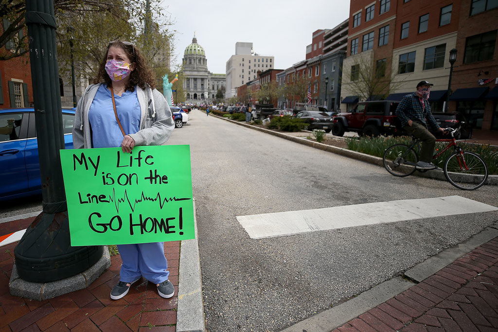 Nurse Erica Zimmerman, of southwestern PA, urged protesters who gathered outside the Capitol Complex to go home during a rally in Harrisburg, PA on April 20, 2020. The protesters called for Gov. Tom Wolf to reopen up the state's economy during the coronavirus outbreak. DAVID MAIALETTI / Philadelphia Inquirer