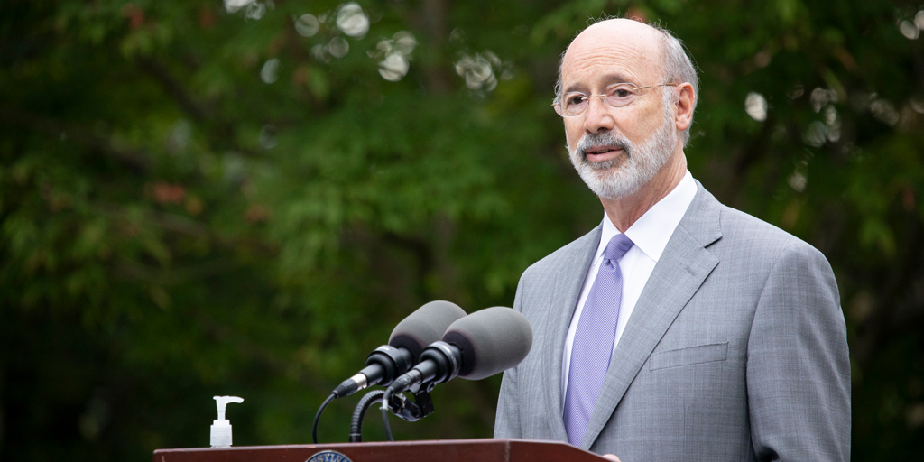 Governor-Wolf-speaking-outside-at-a-podium-with-trees-in-the-background