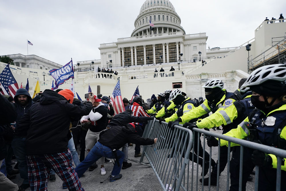 Rioters try to break through a police barrier at the Capitol in Washington on January 6, 2021. AP Photo:Julio Cortez