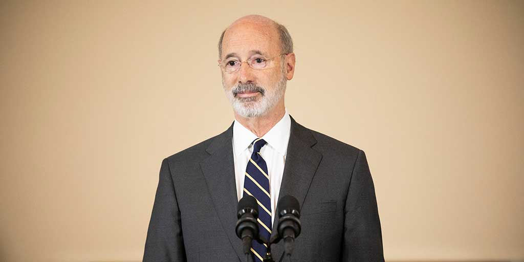 Governor-Tom-Wolf-in-front-of-a-tan-wall