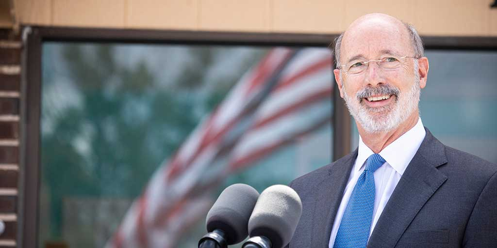 Governor-Tom-Wolf-smiling-outside-in-front-of-a-building