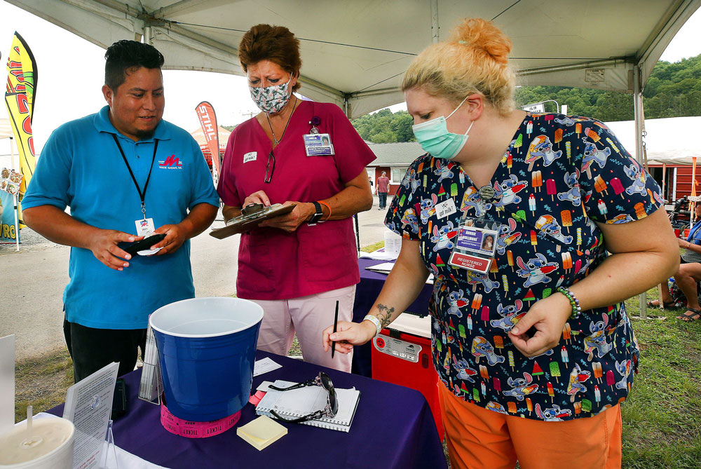 Luis Angel Guzman, a 19-year-old carnival ride worker from Mexico, talks with Wayne Memorial Community Health Center nurses at the Wayne County Fair before he got the Johnson & Johnson vaccine. Photo credit: Fred Adams/For Spotlight PA.
